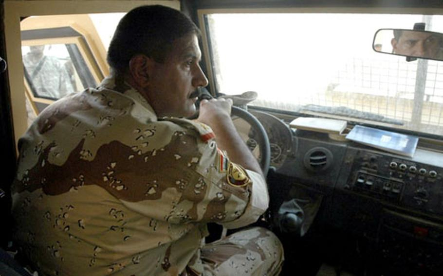 Col. Majeed Mohammed Fatlawi, commander of the 2nd Battalion, 1st Brigade, 8th Iraqi Army Division, sits behind the wheel of one of 10 new armored cars the Najaf unit received recently.