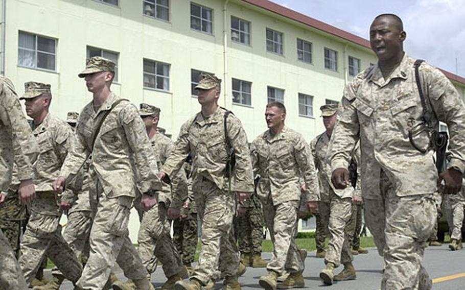 1st Sgt. Hesham Harris calls off cadence to a platoon of 9th Engineer Support Battalion Marines as they march to the battalion's armory at Camp Hansen, Okinawa, on Sunday. About 280 Marines returned from a seven-month deployment in Iraq.