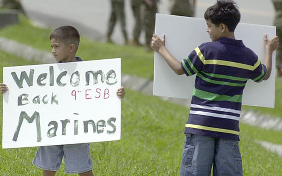 Six-year-old Justin Frye, left, and his nine-year-old brother Shane Frye eagerly wait for their father, Master Sgt. Mark Frye, to arrive at Camp Hansen Sunday after a seven-month absence.