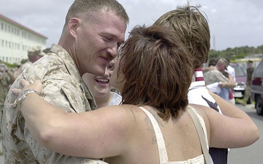 Gunnery Sgt. Shawn Taylor embraces his wife, Rachel, and children: Zech, 14, Emma, 12, and Marissa, 9, after returning from a seven-month deployment.