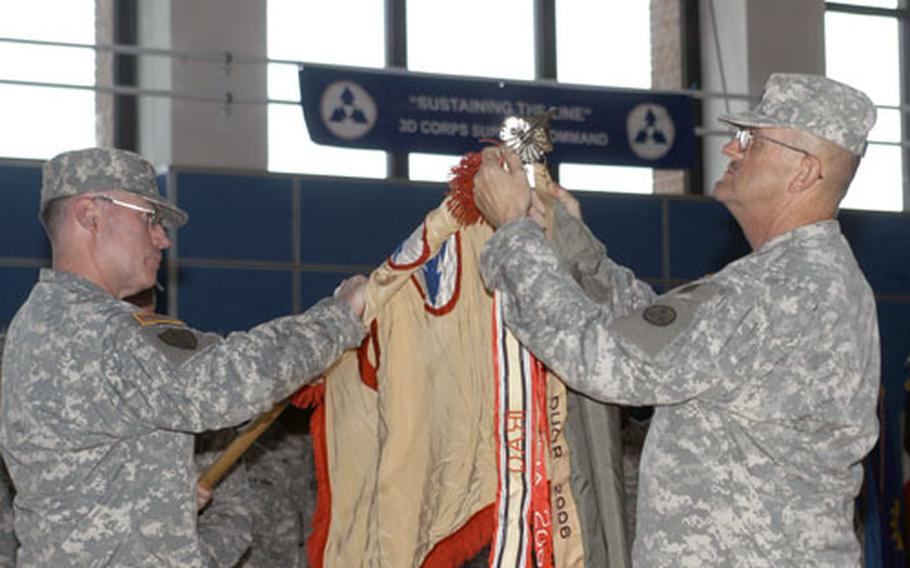 Lt. Col. Thomas E. Kelly, left, commander of the 19th Support Center, and Wallace Sreaves, the unit's command sergeant major, add another battlefield ribbon to the 3rd Corps Support Command guidon to welcome home the troops from a yearlong deployment to Iraq.
