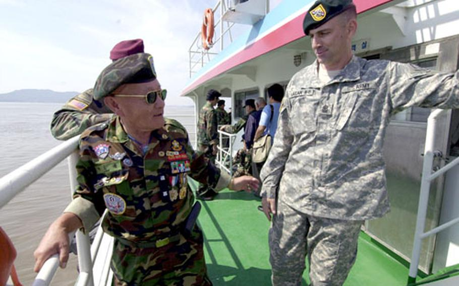 Sgt. Maj. Jack Hagan, of the 39th Special Forces Detachment, chats with a member of the Federation of Partisan Forces Korea during a ferry ride to Kyodong Island on Tuesday.
