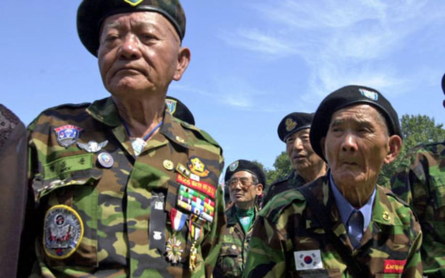 Members of the Federation of Partisan Forces Korea stands in formation on Kyodong Island during a ceremony Tuesday to honor their fallen fellow veterans who died during the Korean War.
