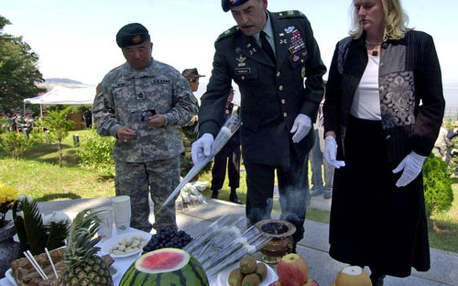 Col. Simeon G. Trombitas and his wife Kellie place flowers on a memorial during a service hosted by the Federation of Partisan Forces Korea on Kyodong Island on Tuesday.
