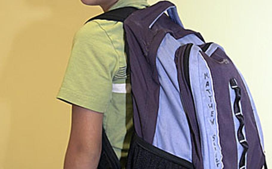 Matthew Sander, 7, demonstrates the correct way to carry a backpack as part of National School Backpack Awareness Day. The pack rests at the curve of Matthew's back.