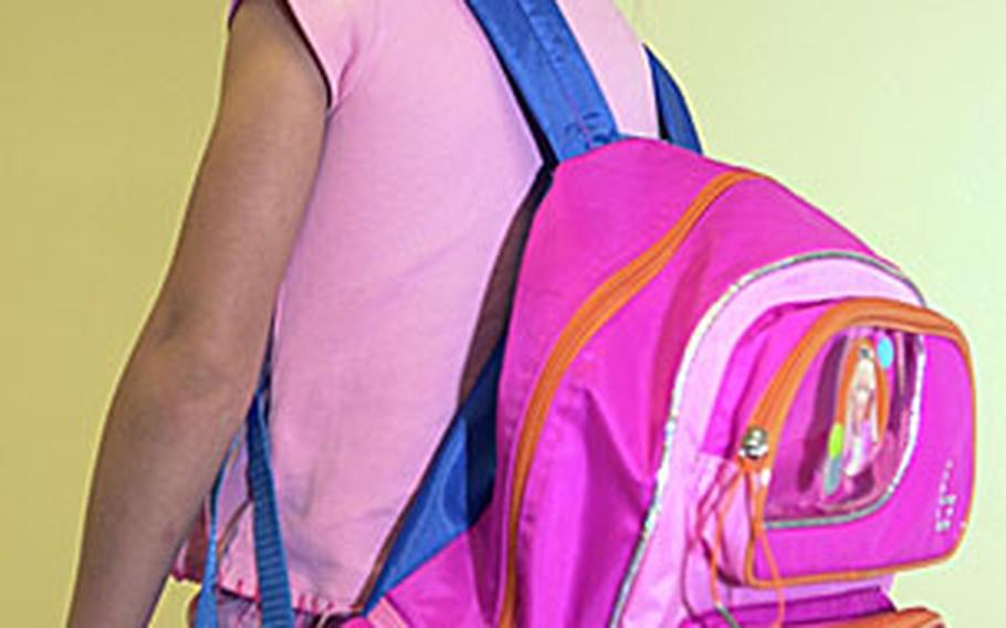 Allison Sander, 6, demonstrates the incorrect way to wear a backpack. Her shoulder straps are not properly adjusted, which allows the pack to hang too low and shift on her back.