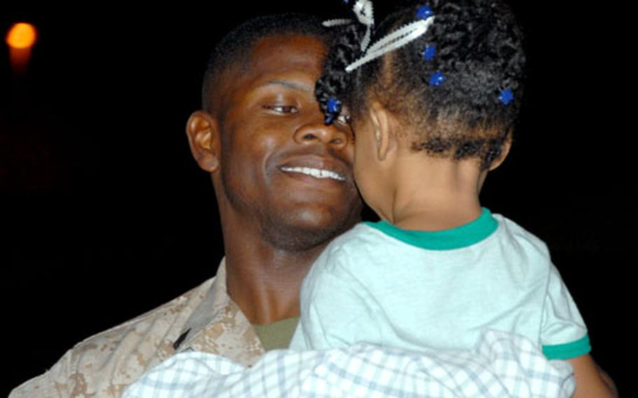 Sgt. Willie Carr hugs his sleepy two-year-old daughter for the first time in seven months early Monday morning. Carr was deployed to Iraq with the 3rd Transportation Support Battalion.