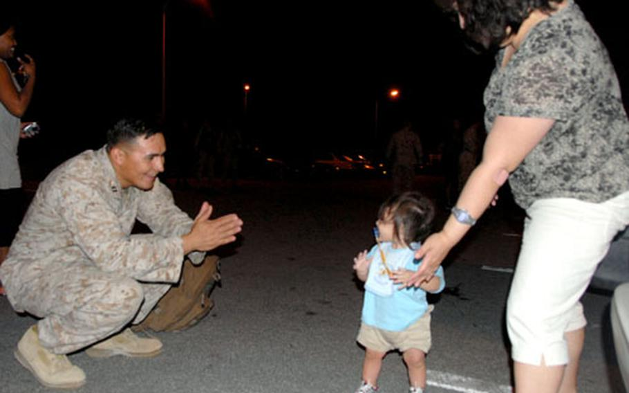 Capt. Ronney Herrera cheers on his one-year-old son as he watches him walk for the first time. His wife, Rae Herrera, right, sent him a photo almost every day of his son, who was only four months old when Herrera's unit deployed to Iraq.
