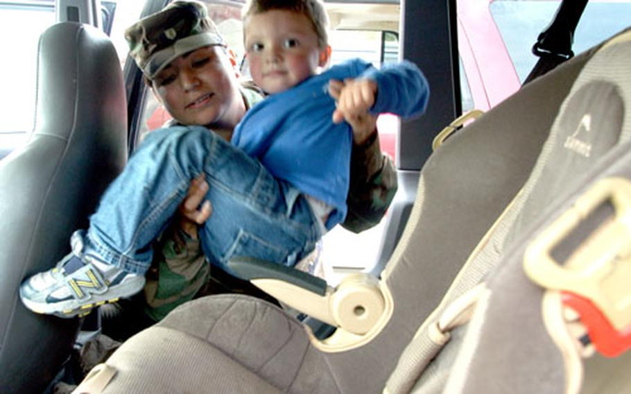 Staff Sgt. Valerie Smith loads her son, Gabriel, into his rear car seat.