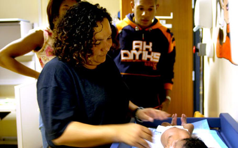 Dr. (Capt.) Maria Perez-Johnson checks out two-week-old Zoë King at the Lakenheath pediatrics clinic recently while the infant's parents, Cavaris and William King, look on.