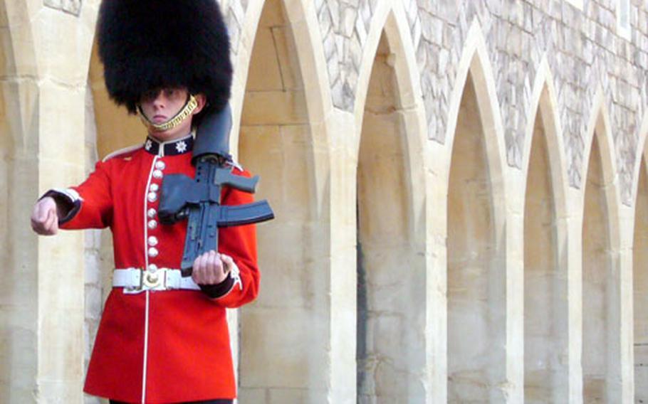 A guard wearing a bearskin hat marches in the lower ward of Windsor Castle.