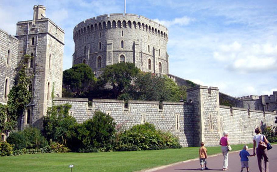 Visitors to Windsor Castle walk past the dominant round tower near the castle's entrance.
