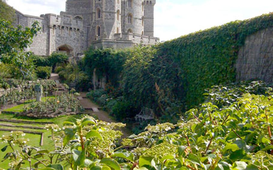 A tower rises above a garden near the entrance of Windsor Castle.