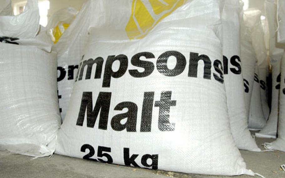 The brewery tour leads past rows of bags of malt and other ingredients.