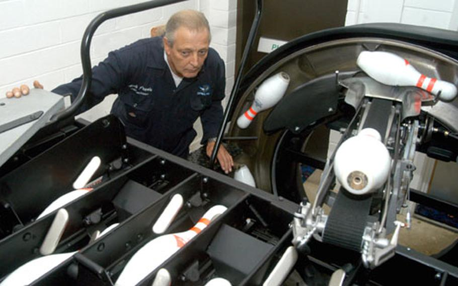Andy Frania, chief mechanic at RAF Mildenhall's bowling alley, inspects an AMF 90XL pinsetter machine last week.