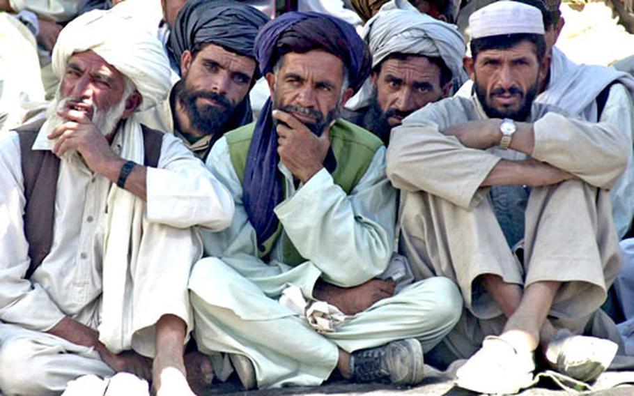 Local men listen during the shura, or meeting, held at the government compound in Miri, Afghanistan on Sunday.