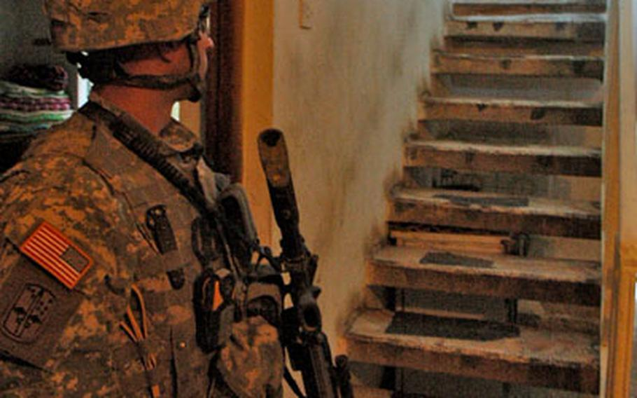 A Company B, 1st Battalion, 17th Infantry Regiment soldier looks up at a young resident during a house search in Baghdad's Shab district.