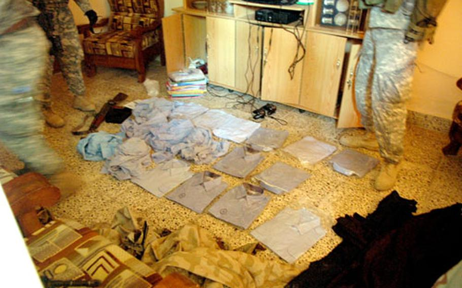 Soldiers from Company C, 1st Battalion, 17th Infantry Regiment sort through contraband - including Iraqi police uniforms - found during a search of two homes in the Shab district.
