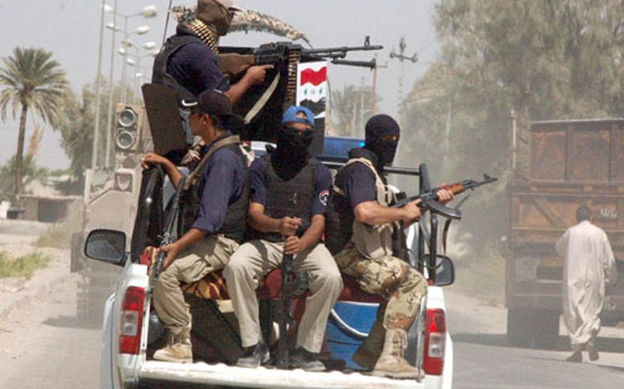 Iraqi police cover their faces to conceal themselves from insurgents as they ride to a raid in Jurf As Sakhir, Iraq.