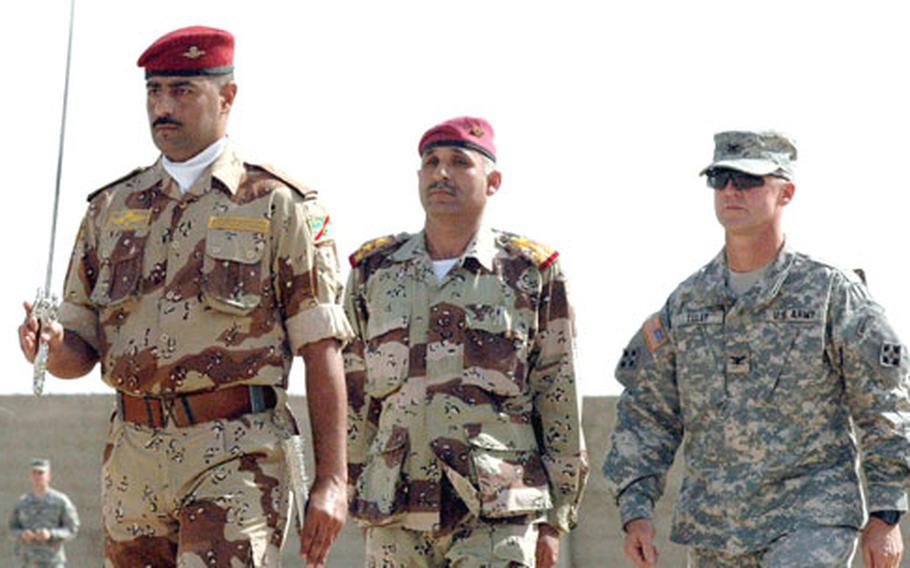 An Iraqi battalion commander leads Iraqi Army Gen. Imad Majhool Somyday and U.S. Army Col. John Tully past Iraqi troops Thursday during a transfer of authority ceremony in northern Babil Province.