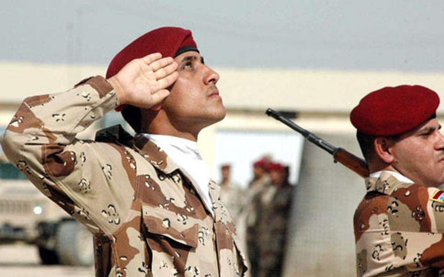 A second lieutenant with the 2nd Battalion, 4th Brigade, 8th Iraqi Army Division salutes his unit colors and his nation's flag.