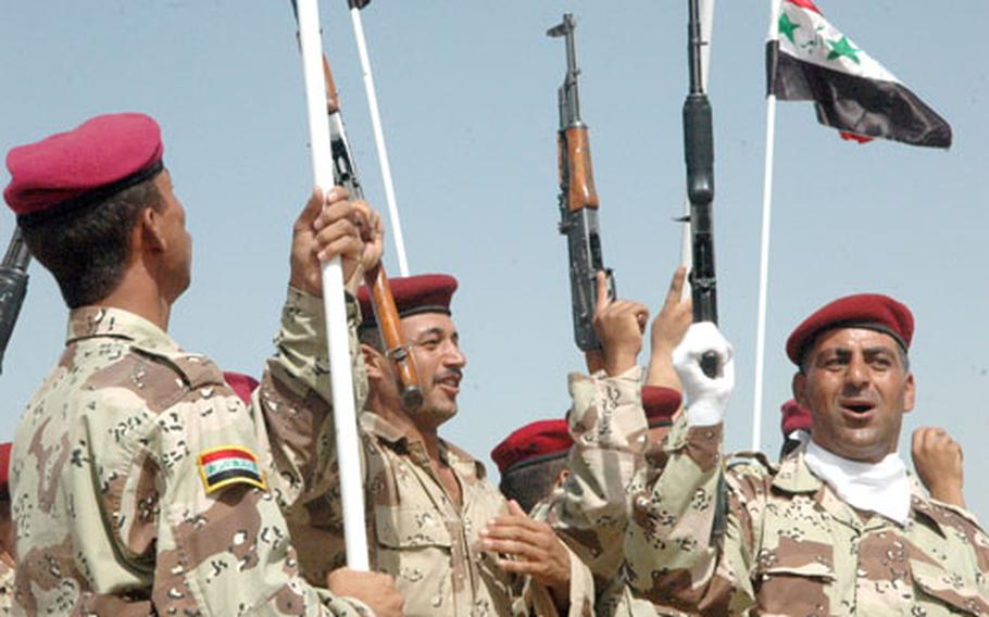 Iraqi army soldiers cheer and raise their rifles Thursday following the ceremony.