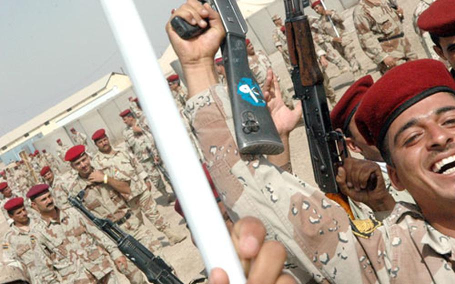 Iraqi army soldiers dance and cheer Thursday following the ceremony