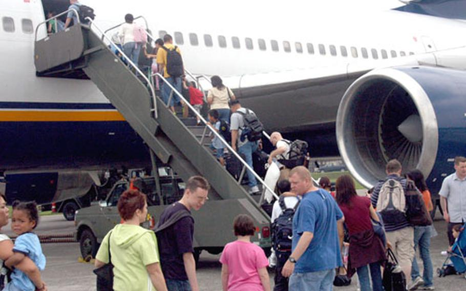 Passengers at Yokota Air Base, Japan, board a Patriot Express flight bound for Seattle this summer. The U.S. military's chartered commercial air service no longer will stop at Misawa Air Base and Iwakuni Marine Corps Air Station after next week.