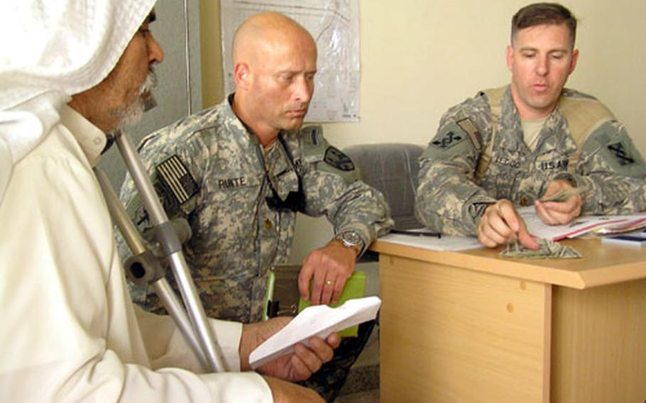Maj. Kyle F. Runte, left, and Maj. Patrick LeDuc pay an Iraqi man U.S. dollars as part of a recent military claims commission in the town of Safwan. War reparations are one way the Army hopes to win hearts and minds in southern Iraq and to help protect U.S. soldiers escorting convoys through the area.