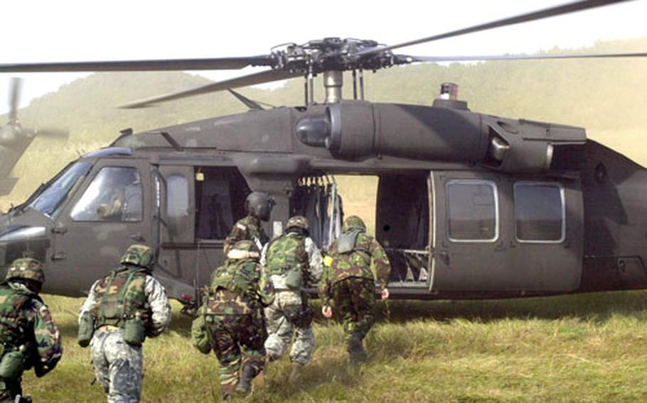 Soldiers from the 8th Army's United Nations Command Security Battalion board the 2nd Infantry Division's Combat Aviation Brigade Blackhawk helicopters.