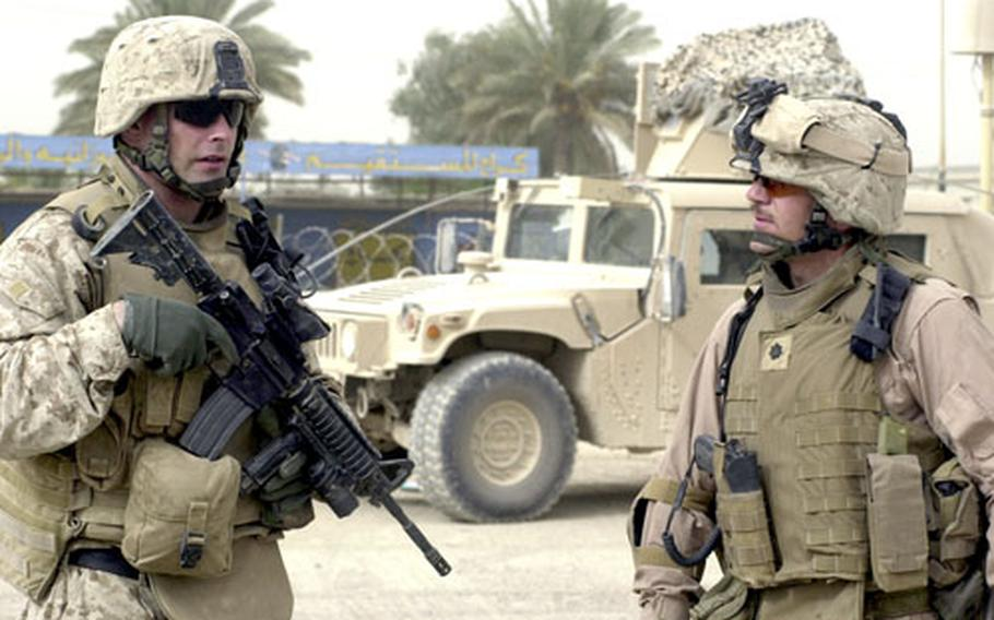 Lt. Col. Todd Desgrosseilliers, right, talks to one of his officers during a hunt for a fugitive connected to a fatal attack on a translator. Desgrosseilliers and other Marines working in Anbar are reviving age-old counterinsurgency tactics that require a heavy presence in the province's most dangerous streets and neighborhoods.