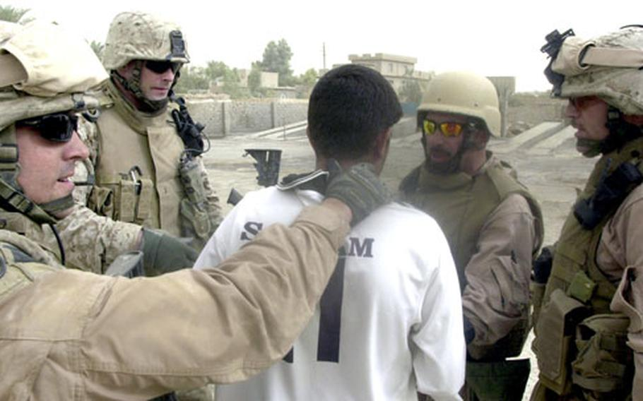 Marines question a teenager in Anbar province about a youth who had just fled and who may have been responsible for a rocket attack the previous day that killed an interpreter. Because he and his Marines are on the street constantly, Lt. Col. Todd Desgrosseilliers, far right, knew the boy and his parents. Rather than arrest the boy, Marines took him to his house and talked to his parents. The Marines were able to find the fugitive that night.