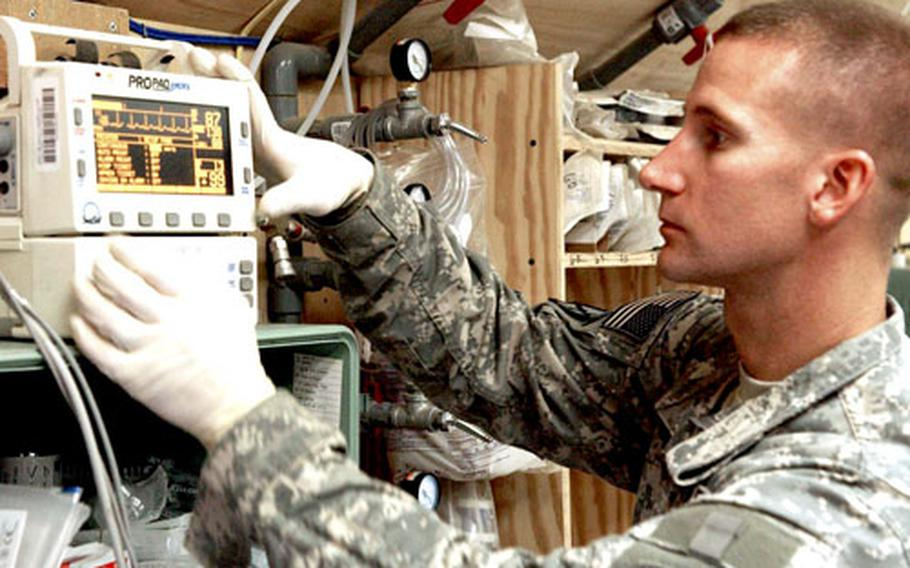 Sgt. Jason Cady checks the vital signs of a patient at the 14th Combat Support Hospital at Bagram Air Base.