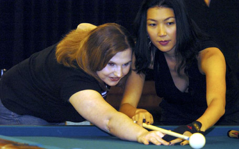 Professional pool player Jeanette Lee instructs Michelle Mcgrath and other servicemembers and civilians on how to shoot pool at the Enlisted Club on Yokota Air Base, Japan, on Saturday.