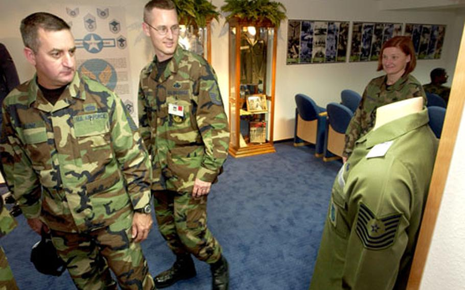 Chief Master Sgt. John Milford, left, the senior enlisted manager of the 435th Civil Engineering Squadron, and Master Sgt. Keith Custer, the first sergeant for the U.S. Forces in Europe Computer Systems Squadron, reminisce about the old green fatigue uniform on display in the new Parish Enlisted Heritage Room.