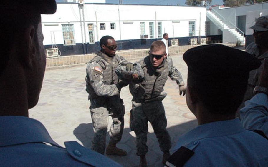 Soldiers with the 1-67 Armor Regiment demonstrate to Iraqi police how to subdue a suspect recently in Musayyib, Iraq.