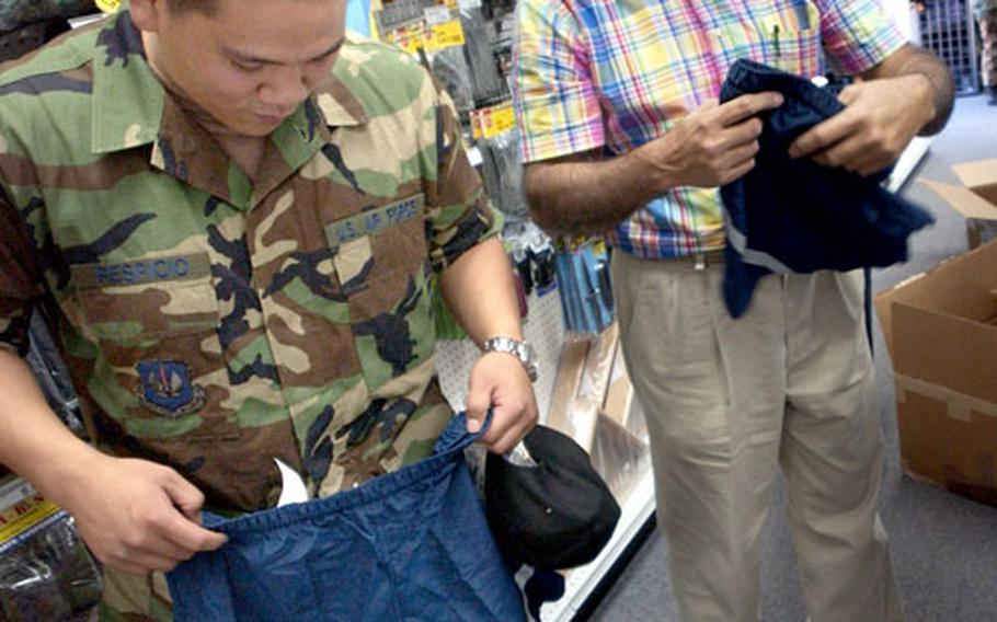 Airman Michael Respicio, from the 435th Logistic Readiness Squadron, checks to see if one of the available size PT gear shorts will fit at the Ramstein Air Base clothing sales store Friday.