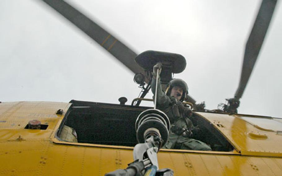 Flight Sgt. Dave Sheppard holds a cable lifting a training participant onto the helicopter.