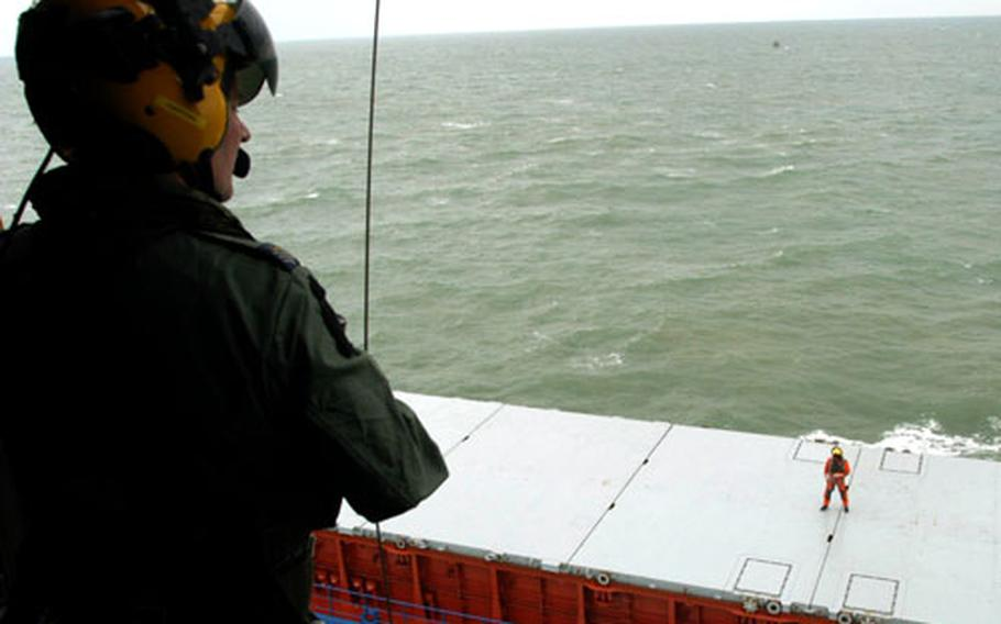 Royal Air Force Sgt. Lee Clark waits on the deck of a freighter in the North Sea for his partner, foreground, Flight Sgt. Dave Sheppard, to lift him into the helicopter during a recent training exercise.
