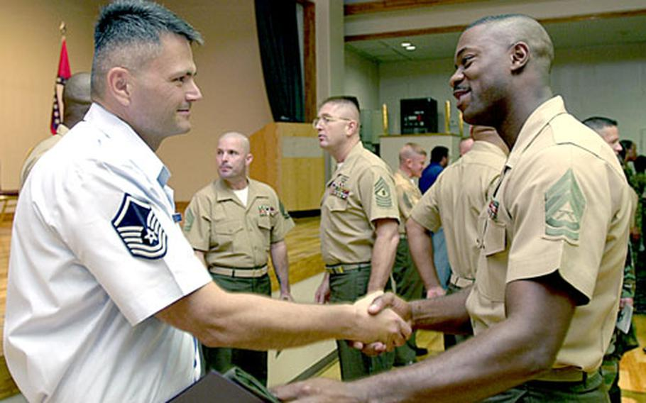 Air Force Master Sgt. Gary Solomon, left, shakes hands with Gunnery Sgt. Howard V. Moore on Tuesday. Solomon participated with 24 gunnery sergeants in Advance Course Class 6-06 at the Staff Noncommissioned Officers Academy.