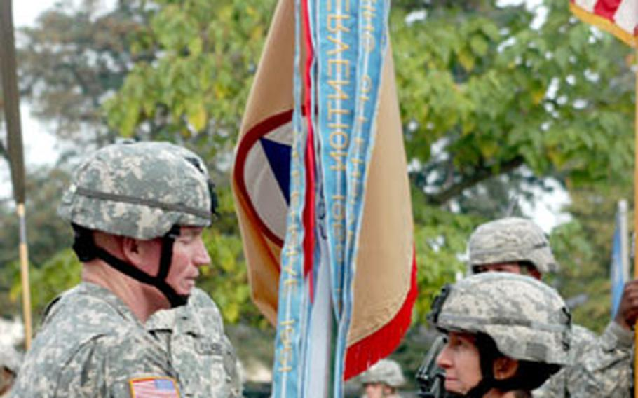 Army Brig. Gen. Scott G. West, left, and Brig. Gen. Becky Halstead take part in the traditional passing of the unit guidon during her change of command ceremony Thursday in Wiesbaden, Germany.