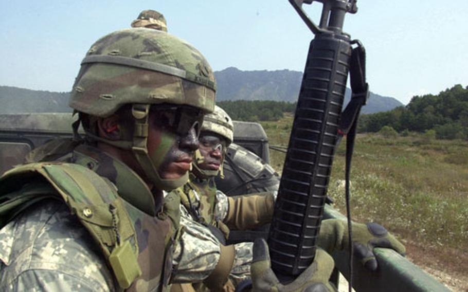 Pfc. John Kreuger, front, and Spc. Roberto Nelson, both of the 501st Special Troops Battalion, stay alert as they pull out in a convoy during training at Rodriguez Range, South Korea, on Wednesday.