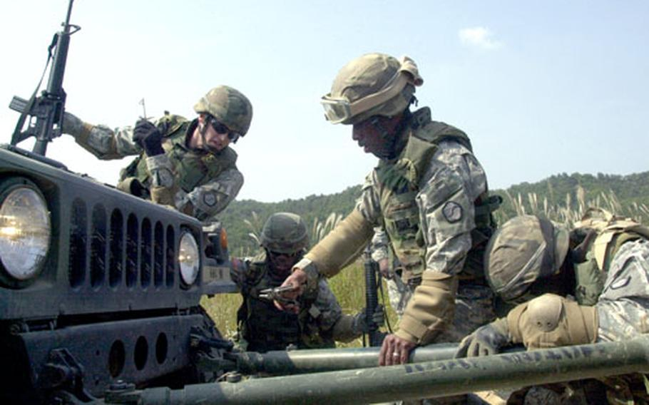 Soldiers for the 501st Special Troops Battalion hook a towbar to a disabled Humvee after a simulated attack during convoy training at Rodriguez Range on Wednesday.