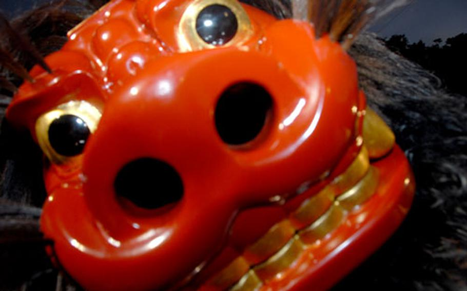 """A shishi, or lion, gets ready to """"bite"""" during a performance Sunday night at the Lion Dance Festival in Uruma. Getting a playful bite from a shishi is considered good luck and is coveted by audience members."""