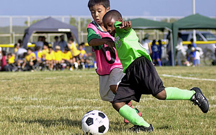 Cindy Fisher / S&S Santino Calloway, front, on the 7- to 8-year-olds Python team, and a Japanese child from the Immatowga Fires team race to the soccer ball during a match Saturday at the Friendship Soccer Tournament at the Chibana Recreation Area. About 580 American and Japanese children participated in the tournament.