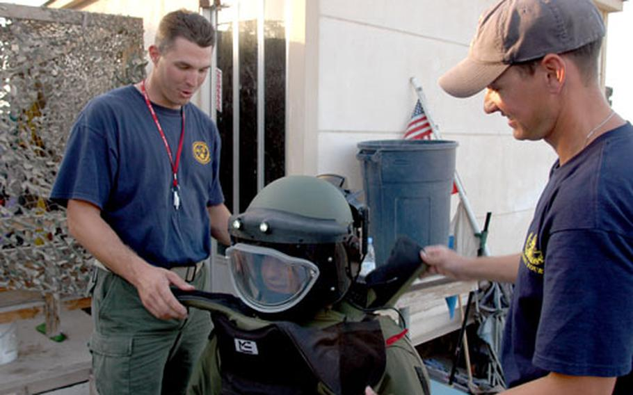 Petty Officer 1st Class Bryen Williams, left, and Chief Petty Officer Kelly Davis suit a soldier up in a bomb suit designed to protect from shrapnel and blast.