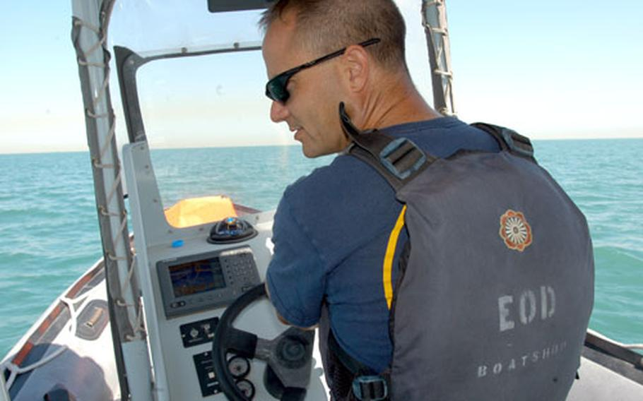 Chief Petty Officer Jeffrey Cooney steers a small boat during training with Naval Coastal Warfare Squadron 354 in a Kuwaiti port on the Persian Gulf Sunday morning.