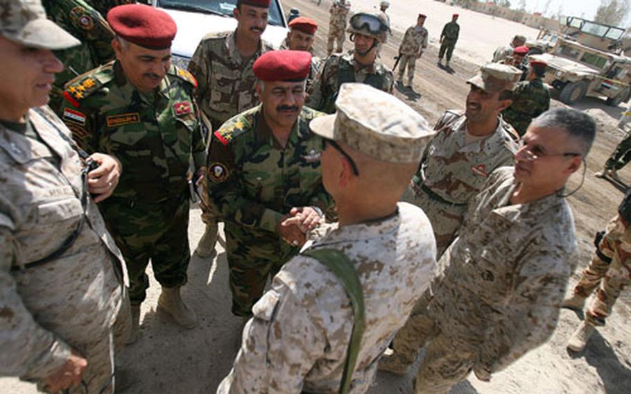 Brig. Gen. Robert Neller (center), deputy commanding general for Mutli-National Forces West, congratulates Iraqi commanders following the transfer of authority from Marine to Iraqi control.