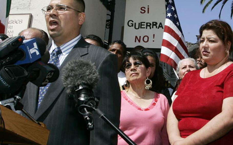 Army Spc. Agustin Aguayo, 34, surrounded by supporters and his wife Helga, right, as he talks during a news conference at Our Lady Queen of Angels Church in Los Angeles on Tuesday.