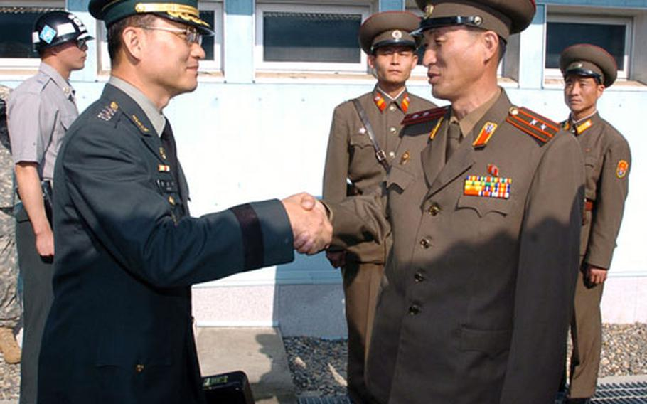 South Korean delegation chief Col. Moon Sung-mook, third from left, is greeted by an unidentified North Korean officer upon his arrival at the North side of Panmunjom on Monday.
